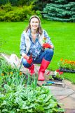 Mujer que trabaja en un jardín de flores Fotos de archivo