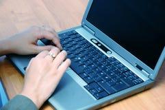 Mujer que trabaja en una computadora portátil Imagenes de archivo