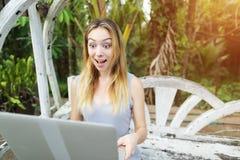Mujer que trabaja independientemente chocada y sorprendida con el ordenador portátil de la PC, fondo de las palmas del verde de l Foto de archivo libre de regalías