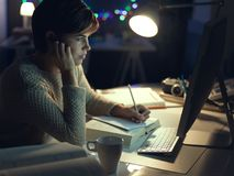 Mujer que trabaja tarde en la noche imagenes de archivo