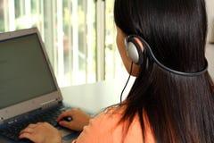 Mujer que trabaja y que escucha la música. Foto de archivo libre de regalías