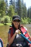 Mujer que transporta en balsa en el río foto de archivo