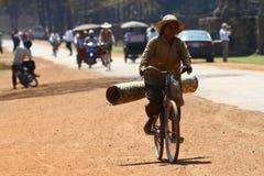 Mujer que transporta la alfombra en la bicicleta Fotografía de archivo