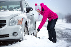 Mujer que traspala nieve de su coche Imágenes de archivo libres de regalías