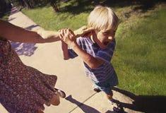 Mujer que tuerce el oído del muchacho Fotos de archivo