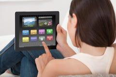 Mujer que usa diversos usos en la tableta digital Imagenes de archivo