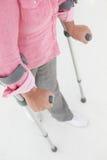 Mujer que usa dos muletas Foto de archivo libre de regalías
