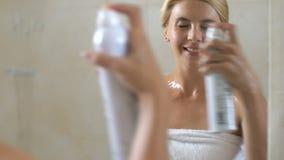 Mujer que usa el agua micelar en cuarto de baño después de la ducha, limpiamiento, entonando la piel metrajes