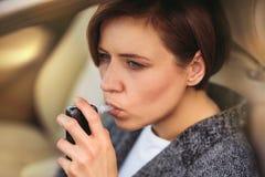 Mujer que usa el analizador del alcohol de la respiración en el coche fotos de archivo
