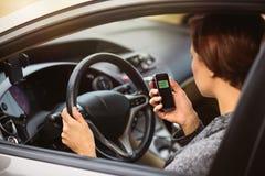 Mujer que usa el analizador del alcohol de la respiración en el coche imagen de archivo libre de regalías