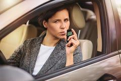 Mujer que usa el analizador del alcohol de la respiración en el coche fotografía de archivo
