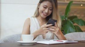 Mujer que usa el app en el smartphone, café de consumición, sonrisa, mandando un SMS en el teléfono móvil almacen de metraje de vídeo