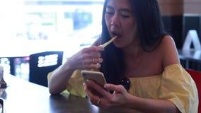 Mujer que usa el app en smartphone metrajes