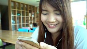 Mujer que usa el app en smartphone en el café de consumición del café que sonríe y que manda un SMS en el teléfono móvil metrajes