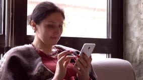 Mujer que usa el app en smartphone en el café de consumición del café que sonríe y que manda un SMS en el teléfono móvil Jóvenes  almacen de video