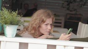 Mujer que usa el app en smartphone en el café que sonríe y que manda un SMS en el teléfono móvil Hembra casual joven multicultura almacen de metraje de vídeo