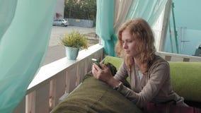 Mujer que usa el app en smartphone en el café que sonríe y que manda un SMS en el teléfono móvil Hembra casual joven multicultura metrajes