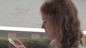 Mujer que usa el app en smartphone en el café que sonríe y que manda un SMS en el teléfono móvil Hembra casual joven multicultura almacen de video