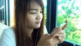 Mujer que usa el app en smartphone en el café de consumición del café que sonríe y que manda un SMS en el teléfono móvil almacen de video