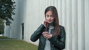 Mujer que usa el App en Smartphone que sonríe y que manda un SMS almacen de metraje de vídeo