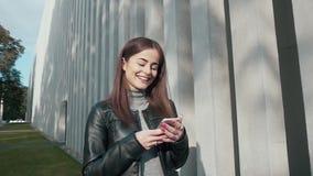 Mujer que usa el App en Smartphone que sonríe y que manda un SMS almacen de video