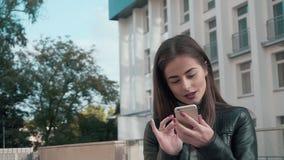 Mujer que usa el App en Smartphone que sonríe y que manda un SMS metrajes