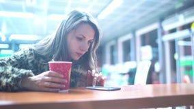 Mujer que usa el app en smartphone y bebiendo el café en café almacen de video