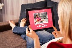 Mujer que usa el app que fecha en línea en la tableta Fotos de archivo