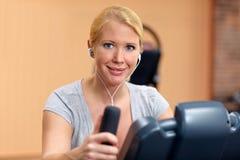 Mujer que usa el bycicle en gimnasia Imagen de archivo libre de regalías