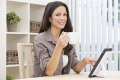 Mujer que usa el café de consumición del té del ordenador de la tablilla Imágenes de archivo libres de regalías