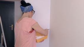 Mujer que usa el cepillo cerca de la esquina de la pared almacen de metraje de vídeo