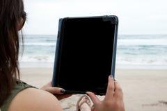 Mujer que usa el dispositivo de la tableta mientras que en una playa Imágenes de archivo libres de regalías
