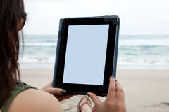 Mujer que usa el dispositivo de la tableta mientras que en una playa Fotos de archivo