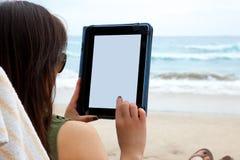 Mujer que usa el dispositivo de la tableta mientras que en una playa Fotografía de archivo
