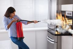 Mujer que usa el extintor para apagar el fuego del horno fotos de archivo