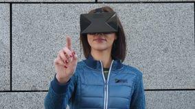 Mujer que usa el finger para tocar en la visión imaginaria del panel en el dispositivo de VR al aire libre Concepto aumentado de  metrajes