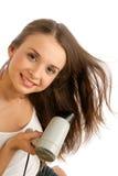 Mujer que usa el hairdryer Imágenes de archivo libres de regalías