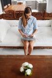 Mujer que usa el hogar del ordenador portátil, relajándose Tecnología de comunicación Fotografía de archivo libre de regalías