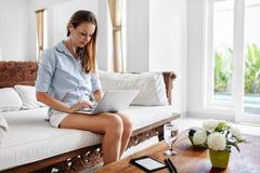 Mujer que usa el hogar del ordenador portátil, relajándose Tecnología de comunicación Foto de archivo