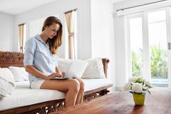 Mujer que usa el hogar del ordenador portátil, relajándose Tecnología de comunicación Fotografía de archivo