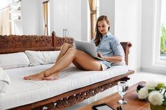 Mujer que usa el hogar del ordenador portátil, relajándose Tecnología de comunicación Imagen de archivo