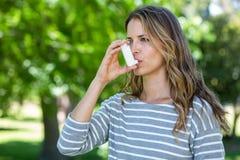 Mujer que usa el inhalador del asma Foto de archivo libre de regalías
