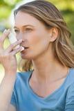 Mujer que usa el inhalador del asma en el parque Imagenes de archivo