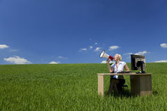 Mujer que usa el megáfono en un campo Imágenes de archivo libres de regalías