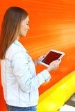 Mujer que usa el ordenador de la PC de la tableta en perfil sobre naranja Foto de archivo libre de regalías