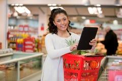 Mujer que usa el ordenador de la tablilla en supermercado fotos de archivo