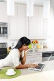 Mujer que usa el ordenador en cocina Imagenes de archivo