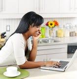 Mujer que usa el ordenador en cocina Imagen de archivo libre de regalías