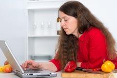Mujer que usa el ordenador en la cocina Foto de archivo