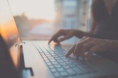 Mujer que usa el ordenador portátil, buscando el web, información de la ojeada, teniendo lugar de trabajo en casa Foto de archivo